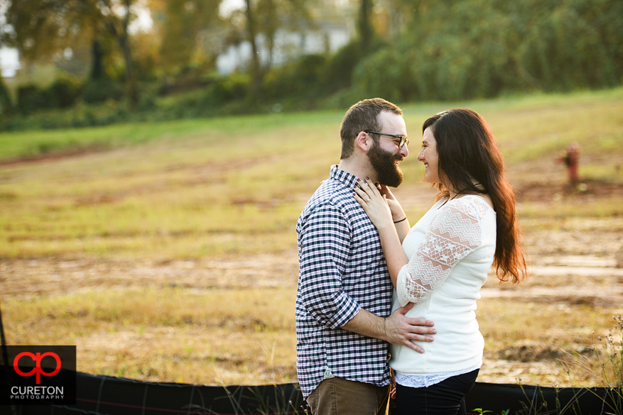 Couple laughing during their engagement session on the Swamp Rabbit Trail in Greenville,SC.