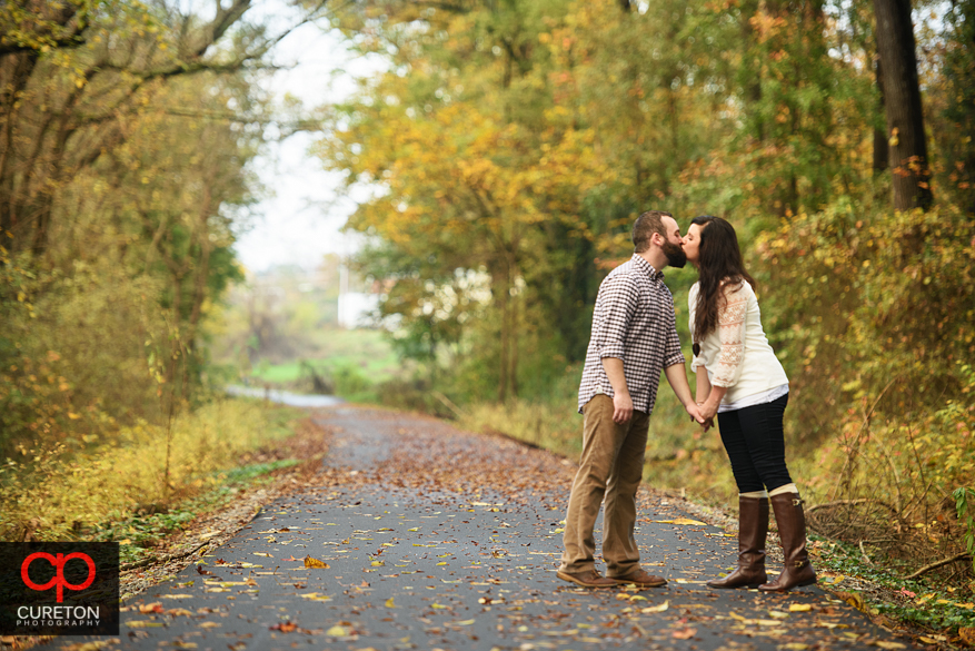 Engaged couple kissing on the leaf covered trial during the fall season.
