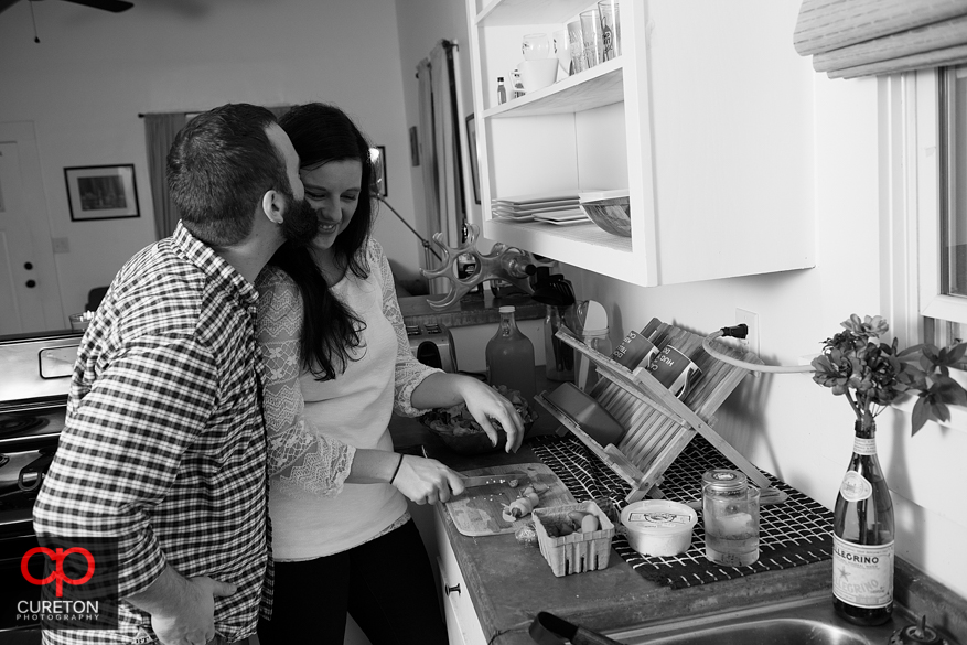 Couple cooking at their house during an engagement session.