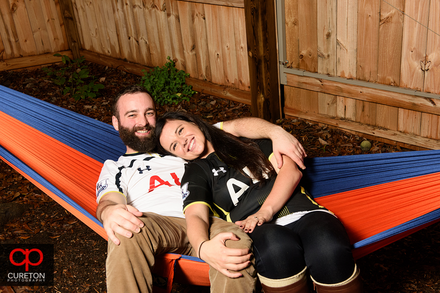 Engaged couple sitting in a hammock.