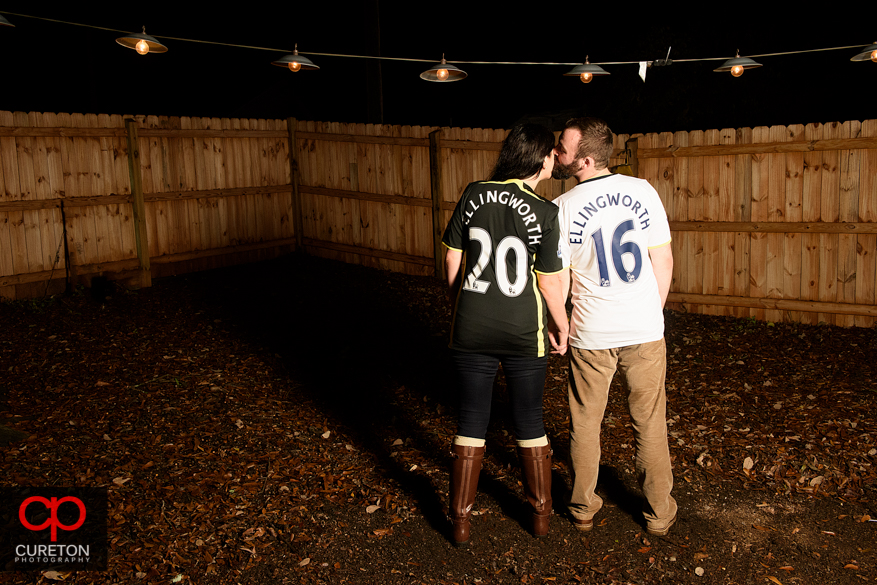 Engaged couple with soccer jerseys on.