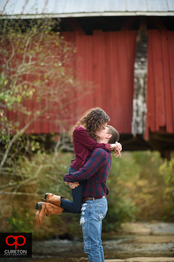 Couple kissing after a Campbell's covered bridge proposal.