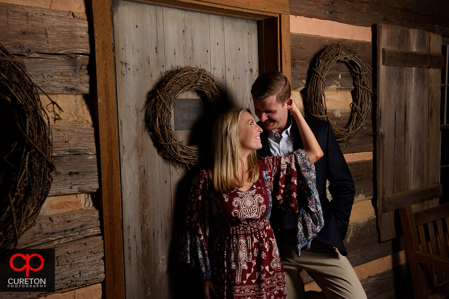 Couple at the Hunt cabin at a Botanical Garden engagement session in Clemson,SC.