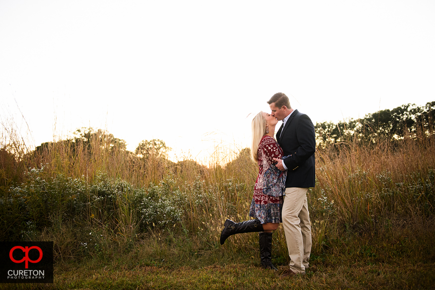 Couple kissing at sunset at a Botanical Garden engagement session in Clemson,SC.