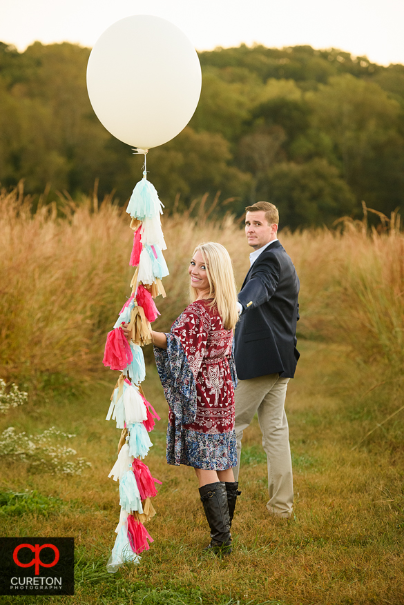 Couple holding a balloon at a Botanical Garden engagement session in Clemson,SC.