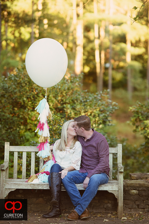 Couple with balloon kissing at a Botanical Garden engagement session in Clemson,SC..