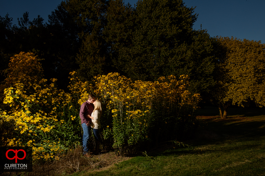Engaged couple standing in flowers at a Botanical Garden engagement session in Clemson,SC..