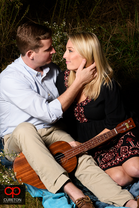 Girl with her fiancee and his guitar at a Botanical Garden engagement session in Clemson,SC..