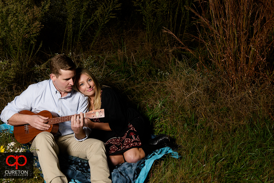 Engagement photo with a couple on a blanket playing guitar.