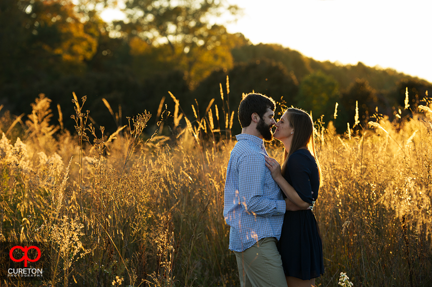 Couple in glowing sun and tall grass during their Botanical Gardens engagement session in Clemson,SC.