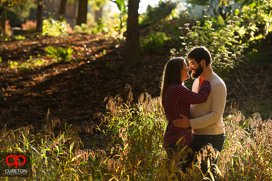 An engaged couple touching foreheads at the Botanical Gardens in Clemson.