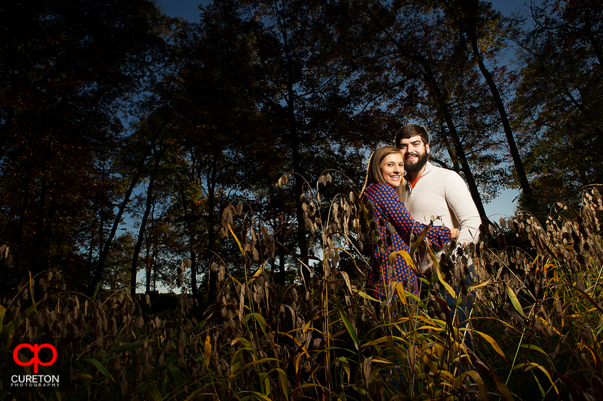 Couple in tall weeds during their Botanical Gardens engagement session in Clemson,SC..