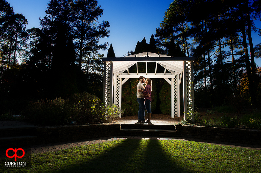 Backlit shot of an engaged couple under a gazebo during their Botanical Gardens engagement session in Clemson,SC.