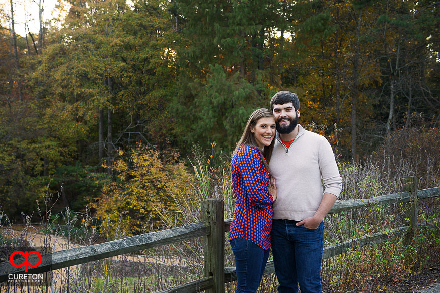 Couple stands near the pond during their Botanical Gardens engagement session in Clemson,SC..
