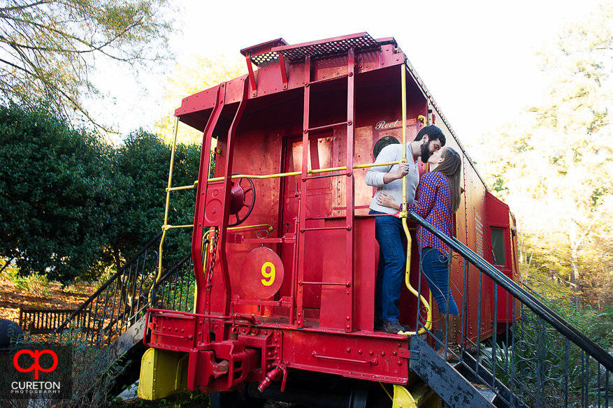 Couple kissing in the train during their Botanical Gardens engagement session in Clemson,SC..