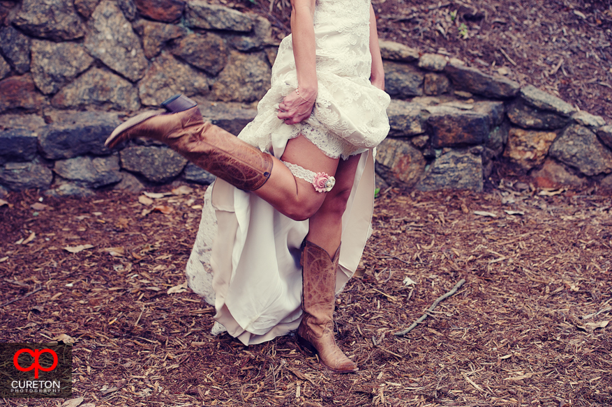 Bride kicking her leg to show off cowboy boots.