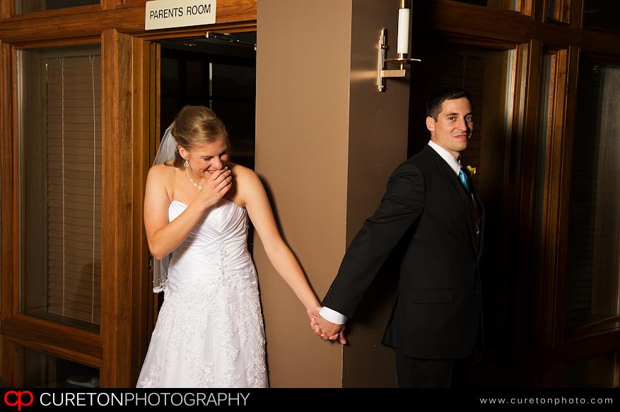 Bride and Groom before wedding on each side of a door.