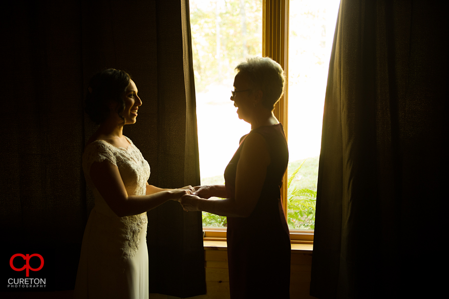 Bride and her mother helping her get ready.