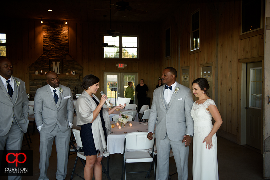 Groom and bride look on as the best man and maid of honor toast the,.