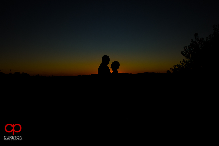 Bride and groom silhouette at sunset.