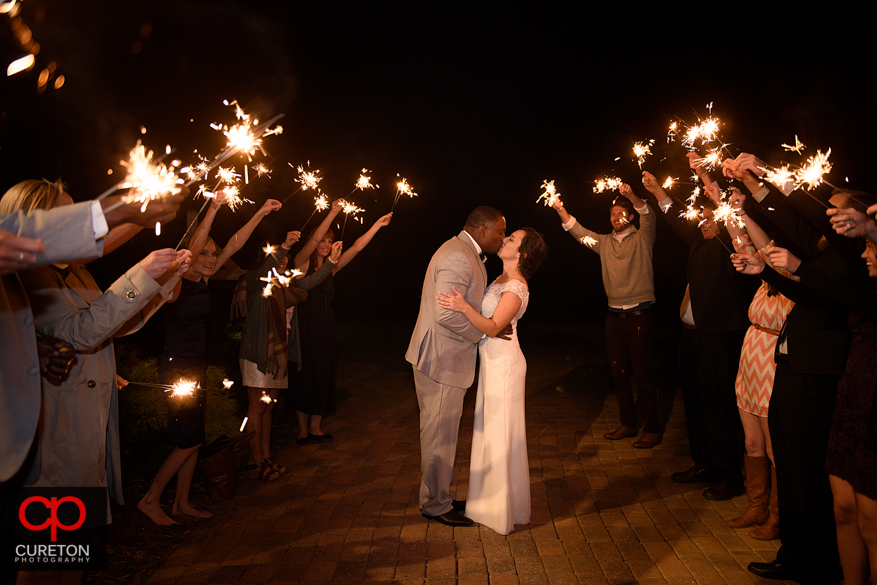 Bride and groom kissing though sparklers.