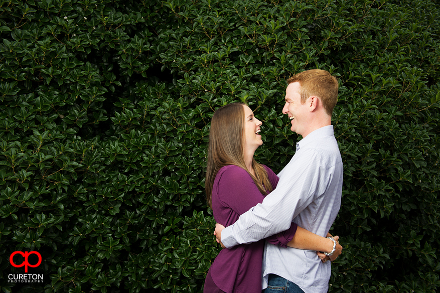 A couple standing in front of bushes near the Amphitheater on Clemson University campus.