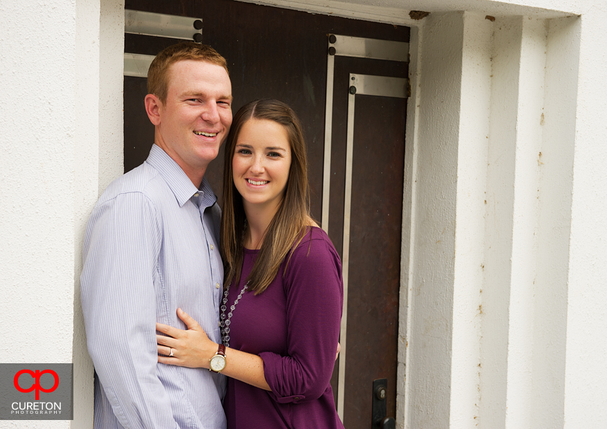 A couple standing in front of a door in Clemson looking at the camera.