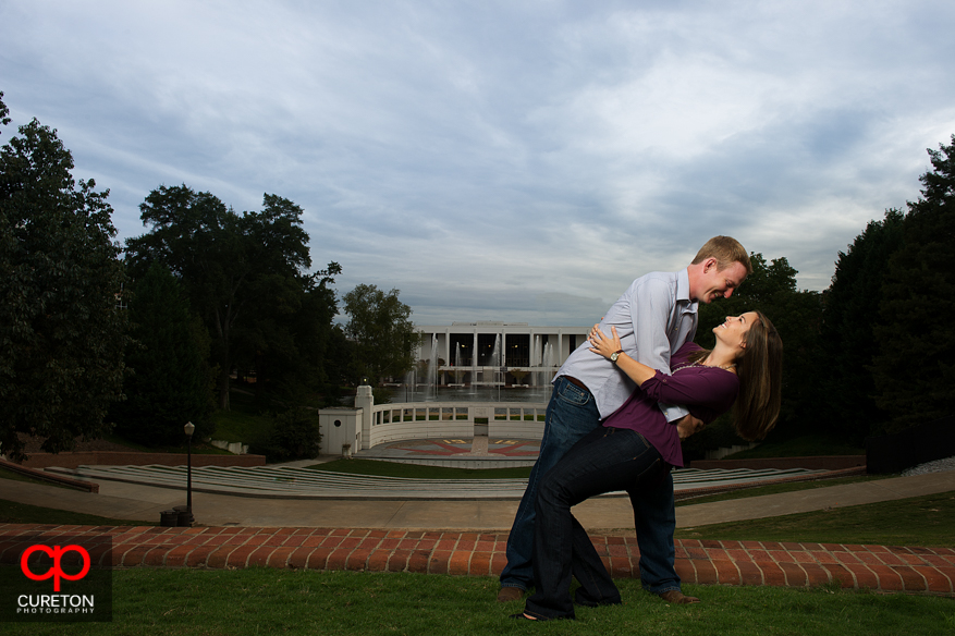 A couple doing a dip in front of the Amphitheater at Clemson University.