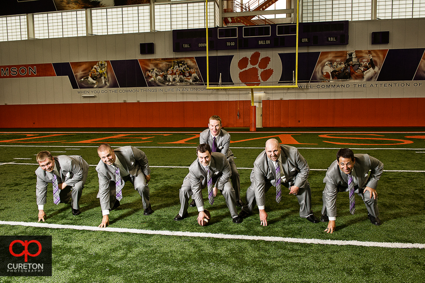 Groom and his groomsmen playing football on the field at the Clemson indoor football complex.