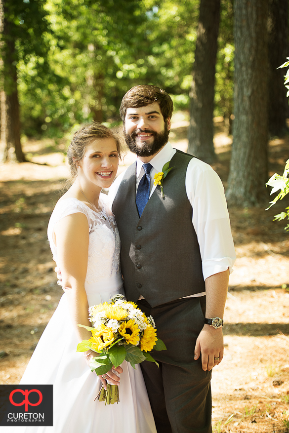 Bride and groom posing in a wooded area.
