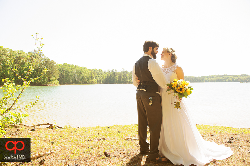 Bride and groom dancing on the beach of Lake Hartwell after their wedding at the Clemson outdoor lab.
