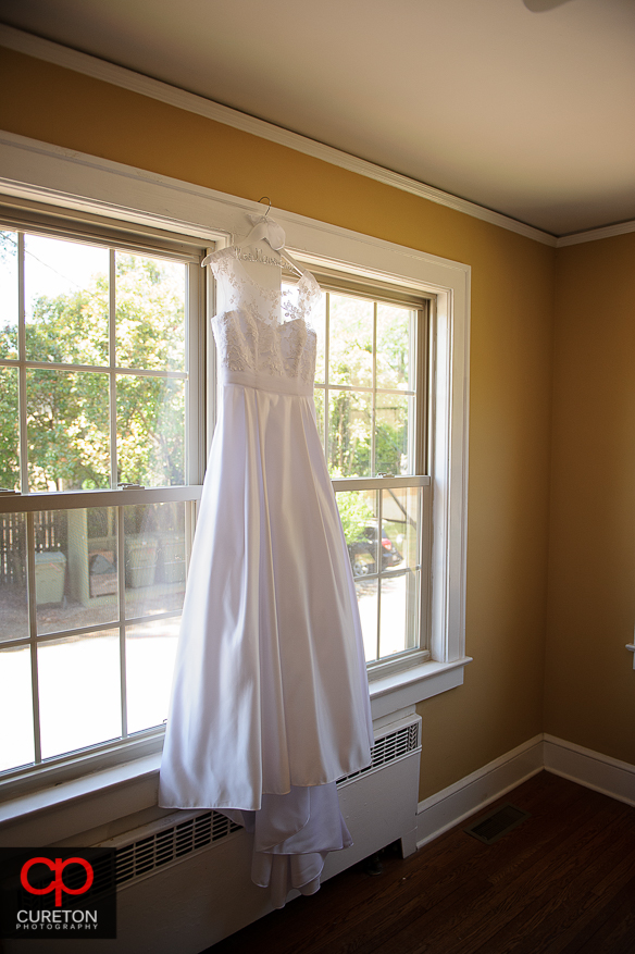 Brides dress hanging in the window.