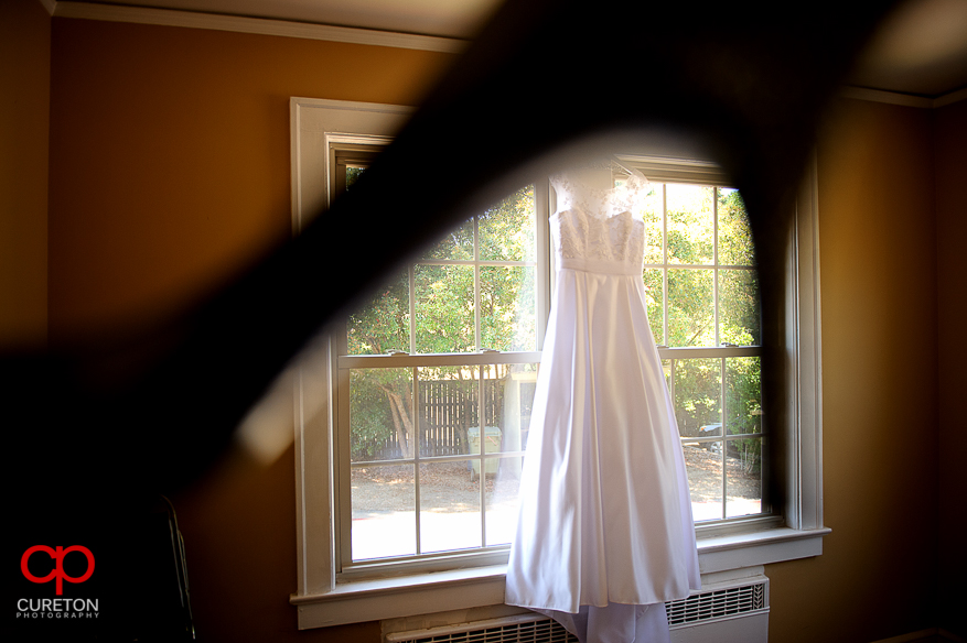 The bride's dress hanging in the window.
