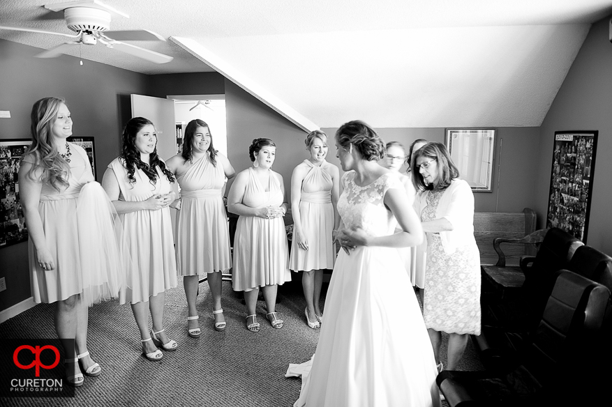 Bridesmaids watch as the mother helps the bride into her dress.