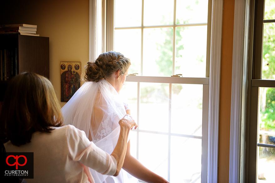 The bride's mother adjust the brides veil.
