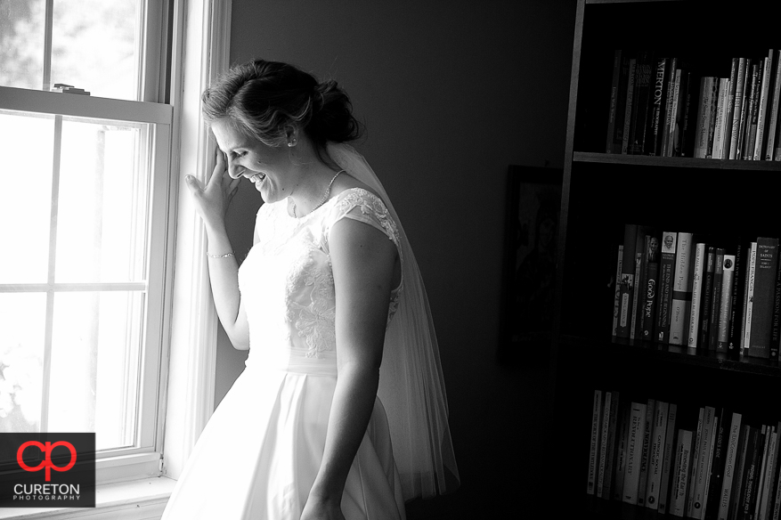 Bride standing next to a window.