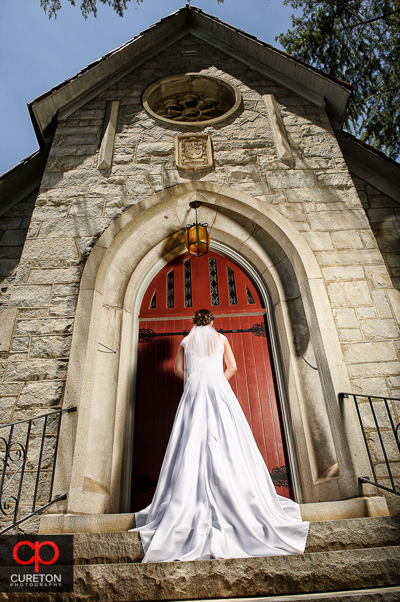 Dramatic shot of the bride in front of a red door at the church.