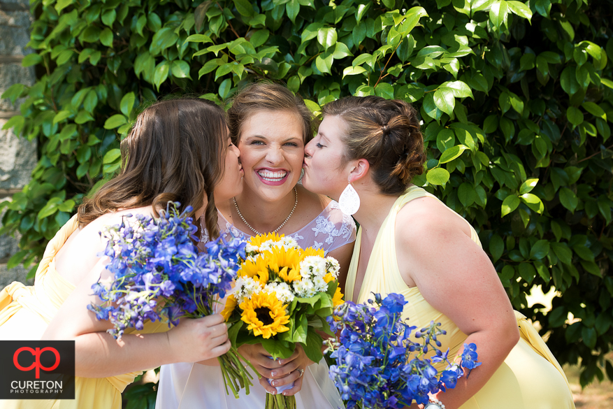 Two bridesmaids kiss the bride on her cheeks.