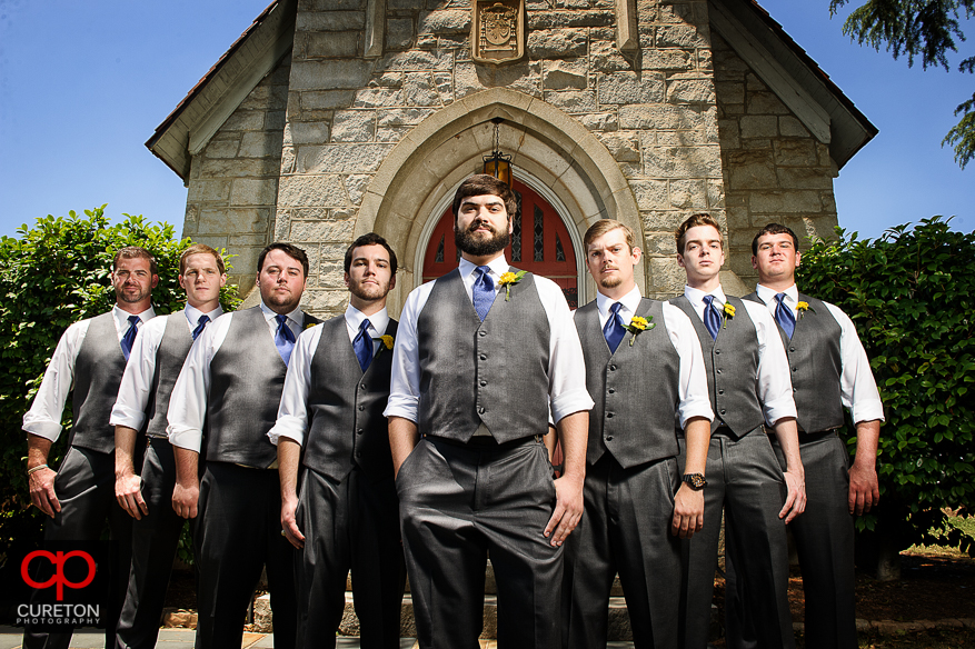 The groomsmen standing in front of the church.