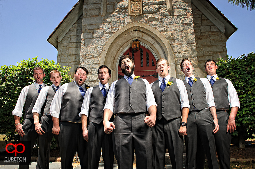 Epic photo of the groom and the groomsmen in front of an old church.