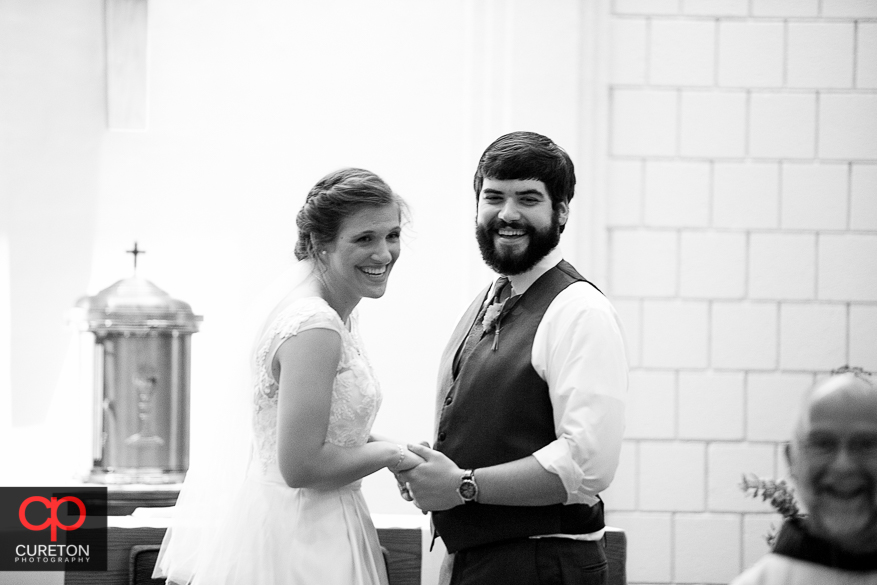 The bride and groom both laughing during their wedding ceremony in Clemson.