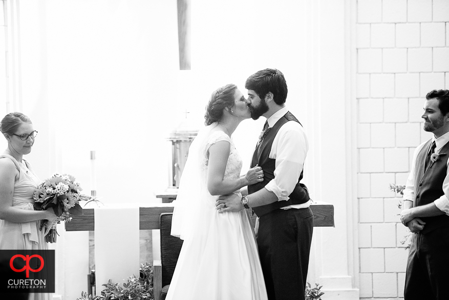 The newly married couple having their first kiss at their wedding.