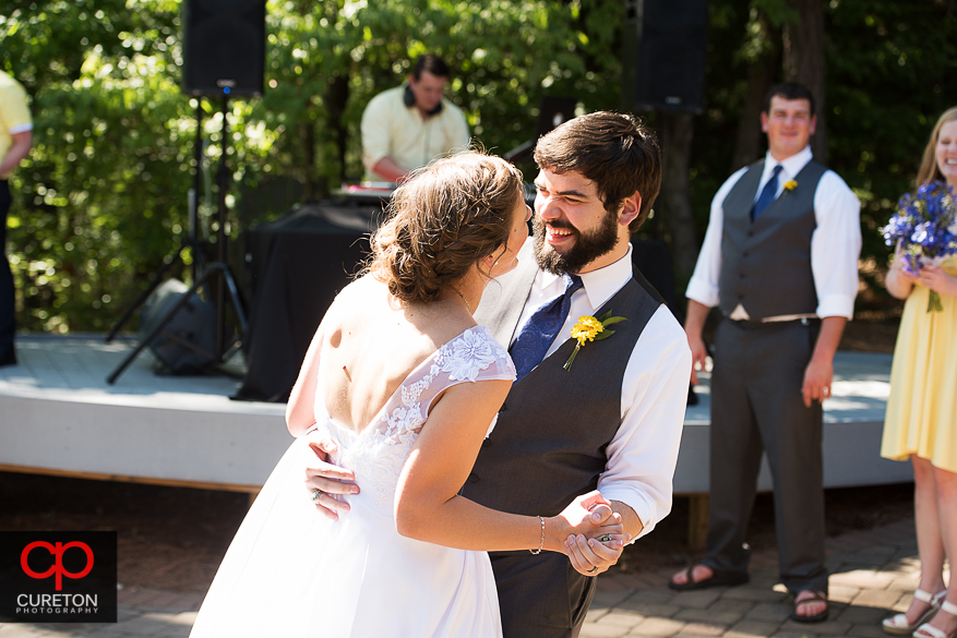 The groom laughing during their first dance at the reception.