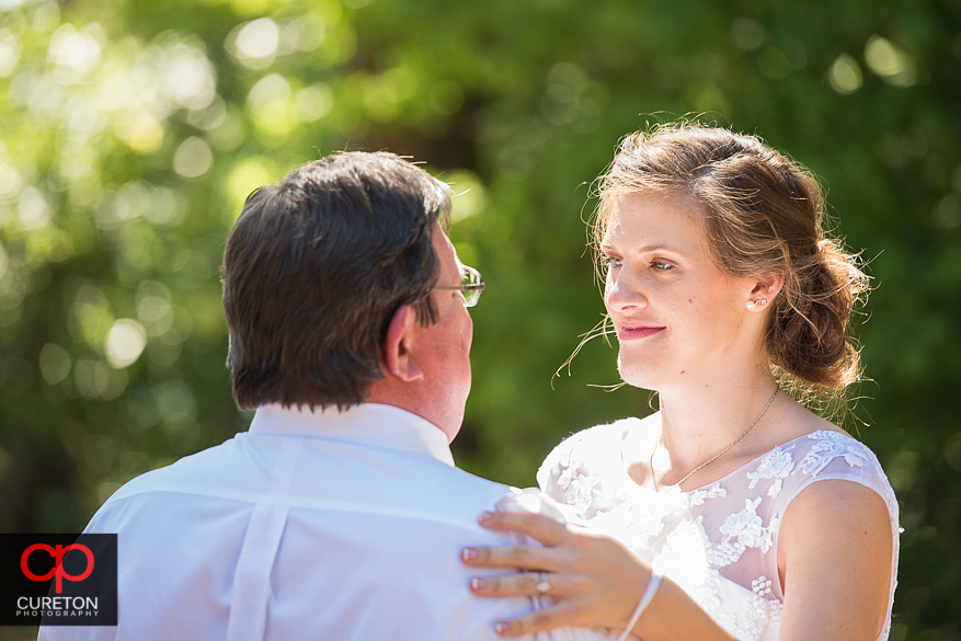 The bride and her father share a dance at her wedding reception.