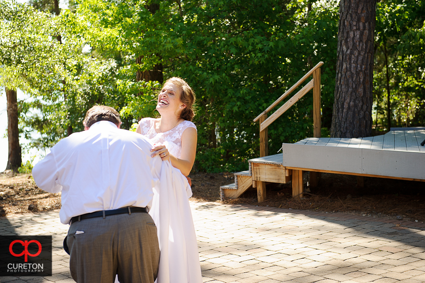 The bride and her father laughing during their dance at the wedding reception.