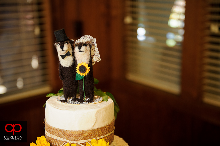 The creative cake topper on top of the wedding cake.