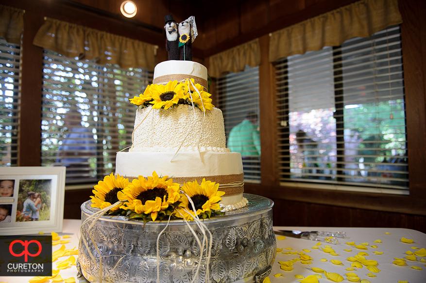 Beautiful wedding cake adorned with sunflowers.