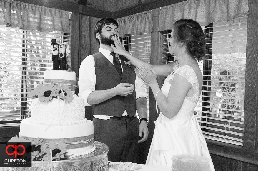 The bride feeding the groom cake at the reception.