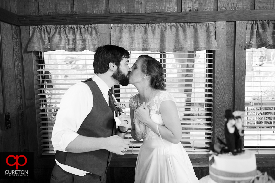 The bride and groom kissing after cutting their cake.