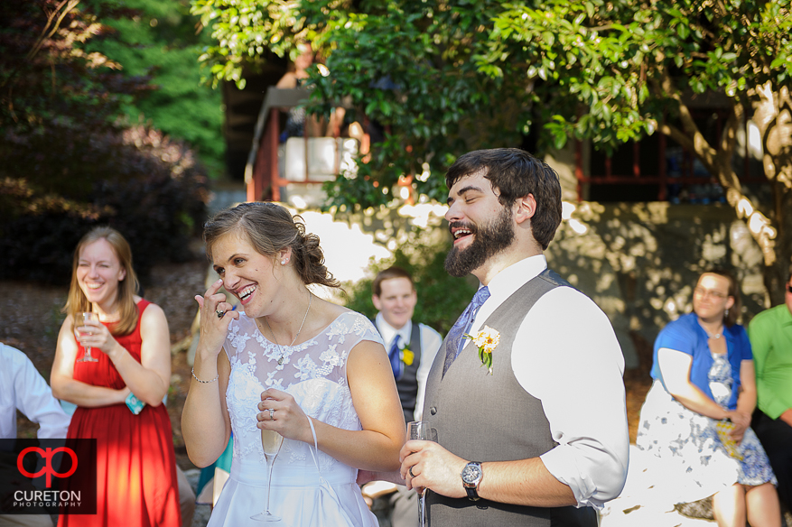 The married couple laughing at the toast at their wedding.